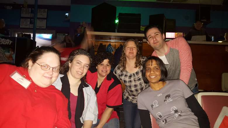 six people sitting at bowling alley seats