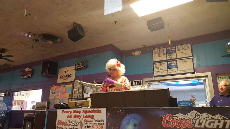 a woman speaking over a loudspeaker in a bowling alley