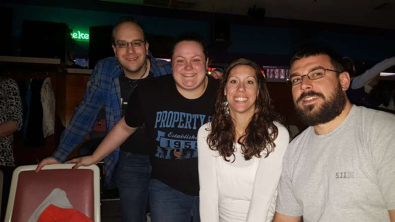 four people at bowling alley seats