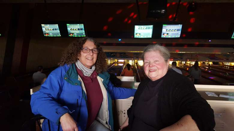 two people sitting together at a bowling alley