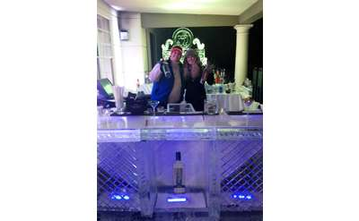 two people standing behind an ice bar