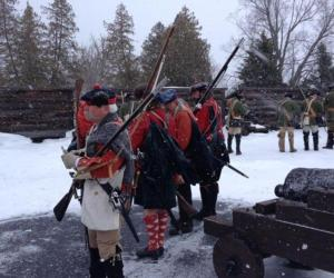 reenactors dressed in period outfits at fort william henry in the snow