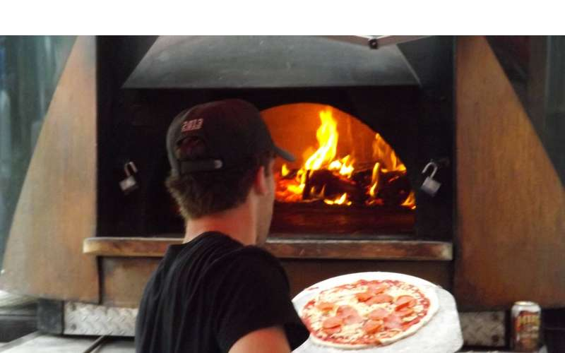 Photo of person cooking pizza