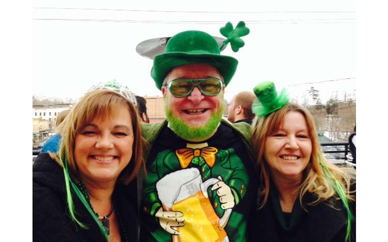 three people smiling at a st patrick's day event