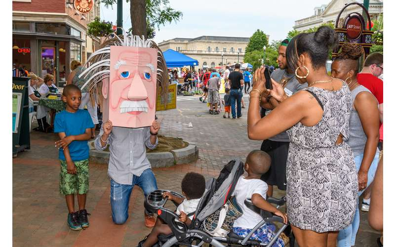 person taking photo of someone with large mask