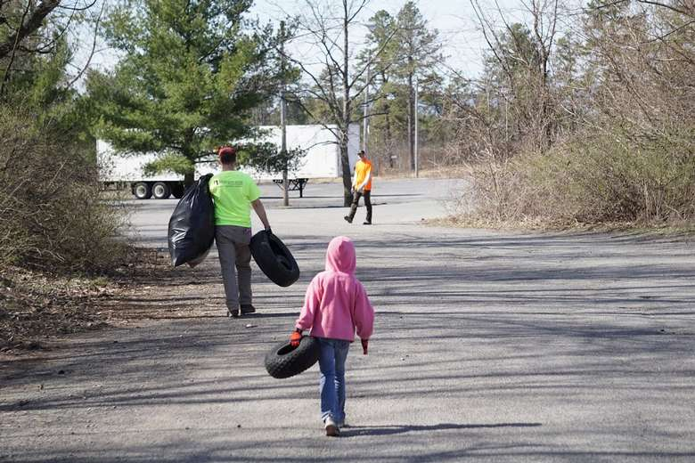 woman and child carrying trash and a tire