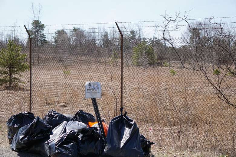 a bunch of trash bags by an Albany Pine Bush Preserve sign