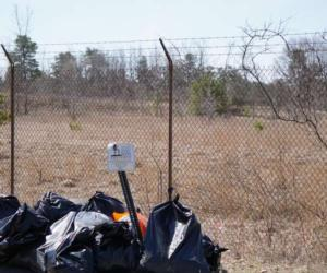 pile of trash bags by an Albany Pine Bush sign