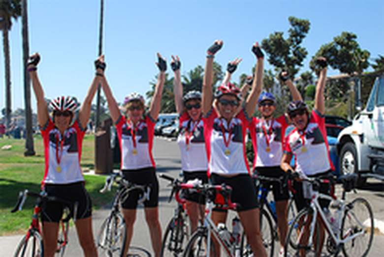 bicycle riders with arms raised