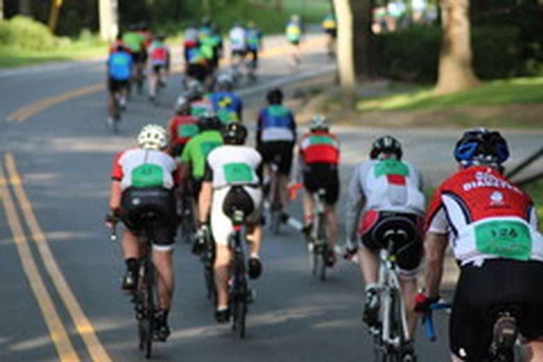 bicyclists riding down a road