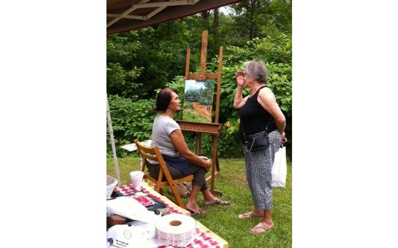 2 women discussing by a painting