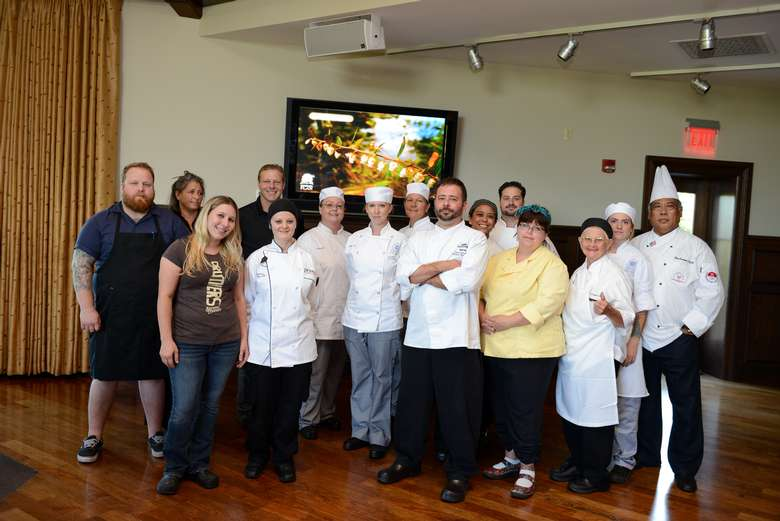 a group of people and chefs posing for a photo