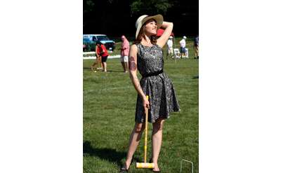 Young women smiling up at the sky and posing with croquet mallet at Croquet on the Green for AIM Services