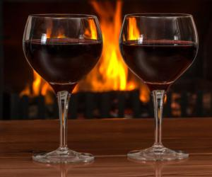 two glasses of red wine with a fire in the background