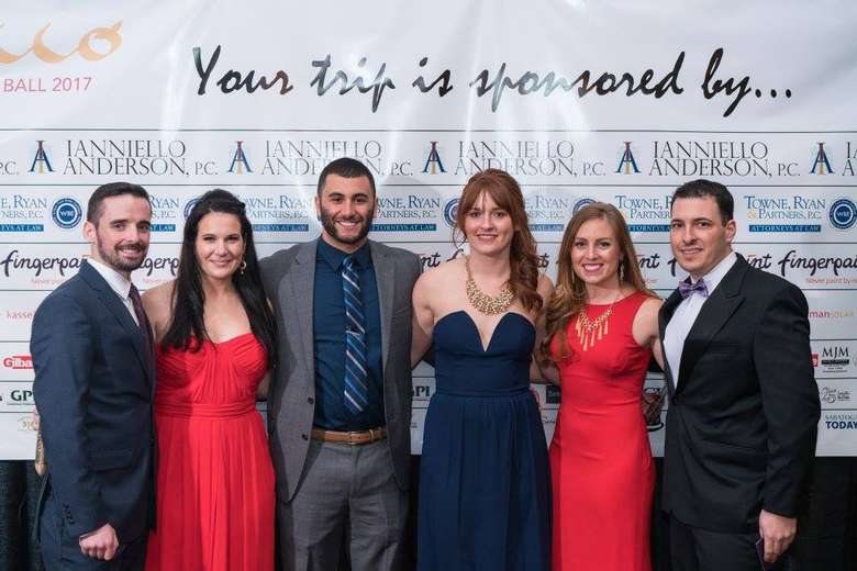 six people at a gala posing for a photo