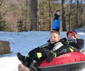 two little boys snow tubing