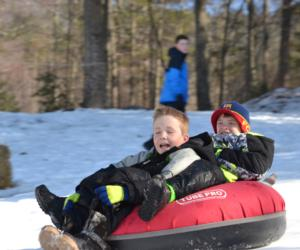 two boys snow tubing