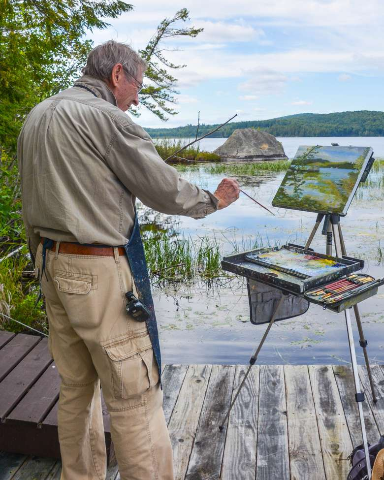 man painting on a dock