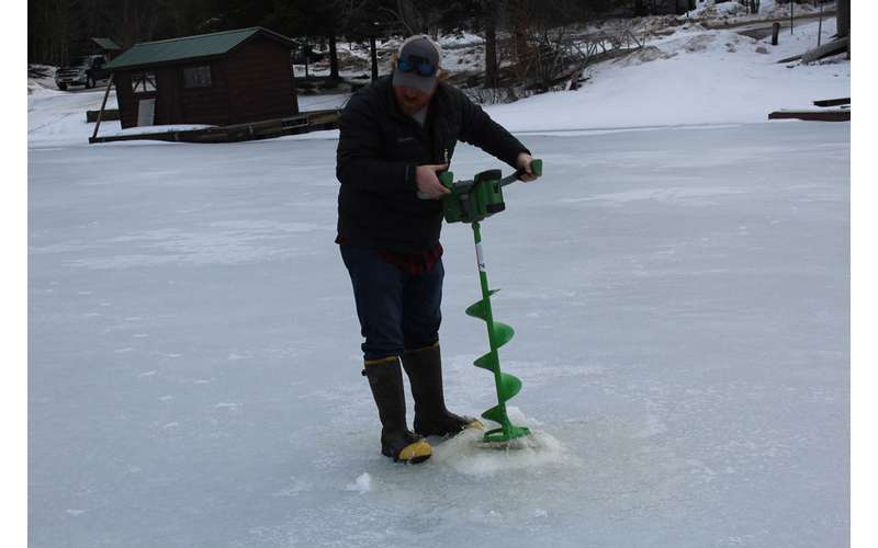 a man digging a hole through the ice