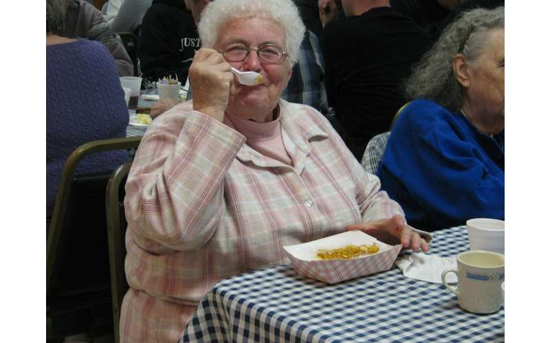 elderly woman eating food at a picnic table
