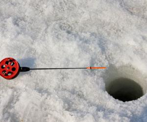 a fishing pole next to a hole in the ice