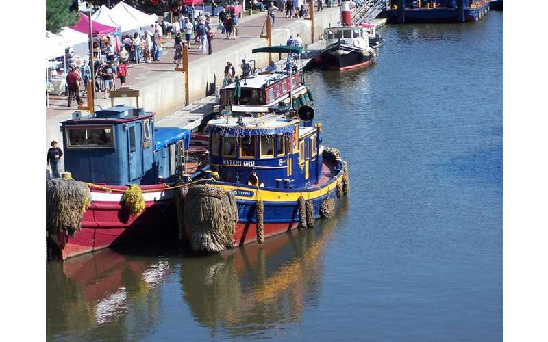 a blue tugboat sitting in the water