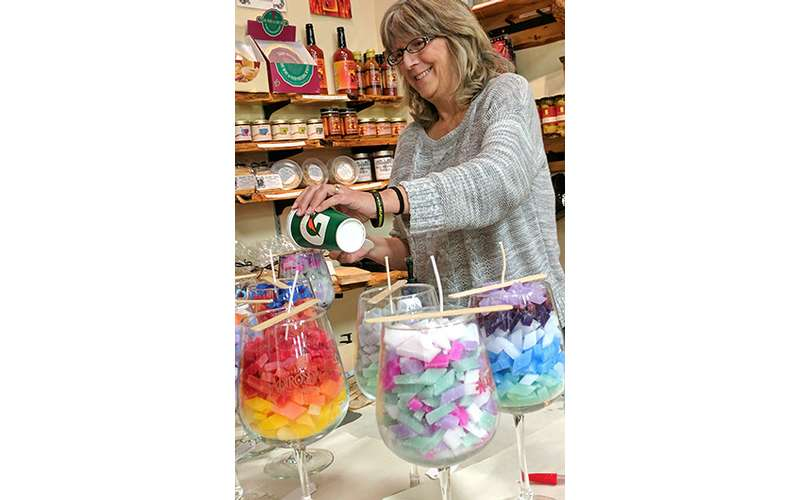 a woman creating some wine glass candles