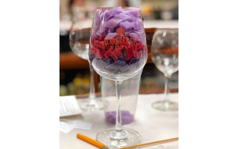 wine glass filled with colorful pieces of wax