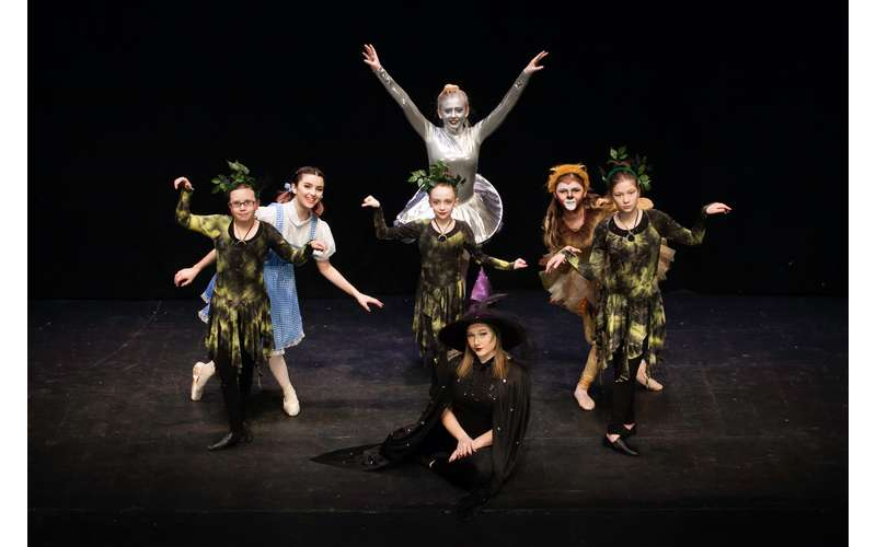 dancers performing as dorothy, the tin man, and other wizard of oz characters