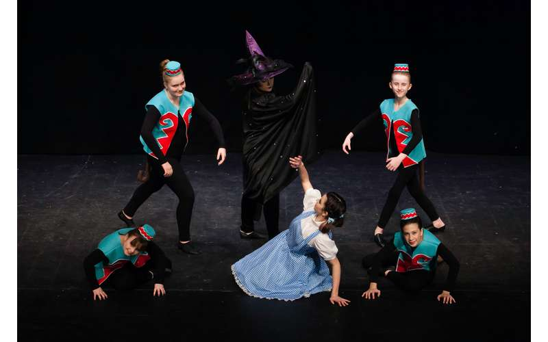 dancers performing as dorothy, wicked witch, and flying monkeys