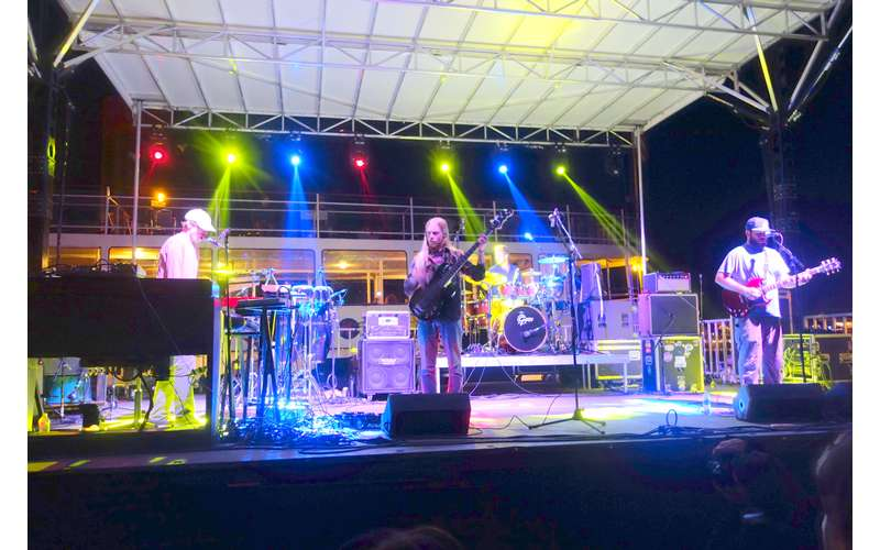 a band performing on stage with colorful lights