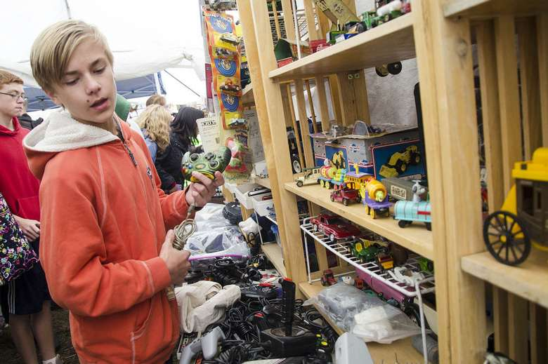 boy browsing toys at garage sale