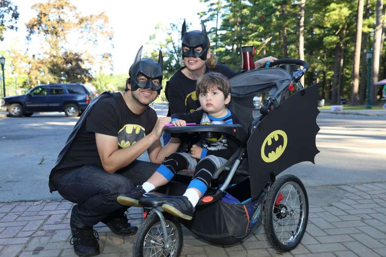 a couple with kid in batman stroller