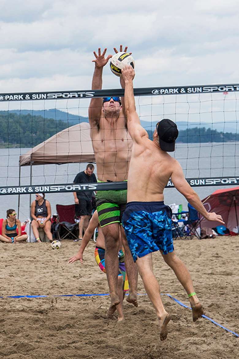 player hitting volleyball over net