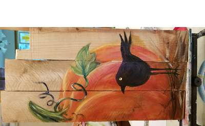 A cropped image of an orange pumpkin and stylized black crow painted on wooden board panel.