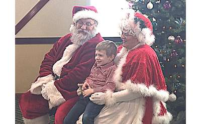 kid posing with Santa and Mrs. Claus