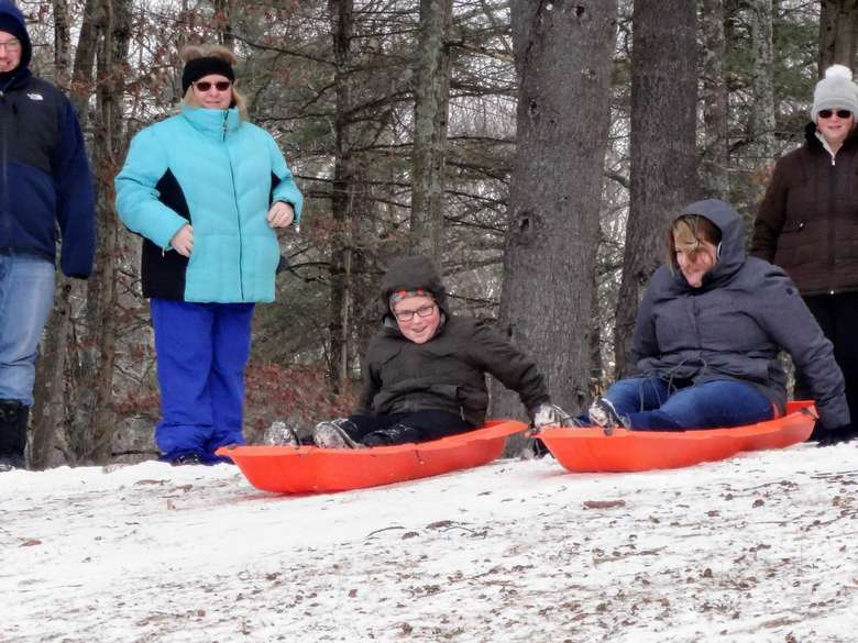 people about to sled down a hill