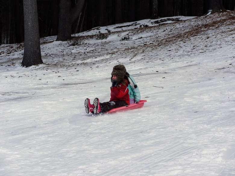 kid sledding down a hill
