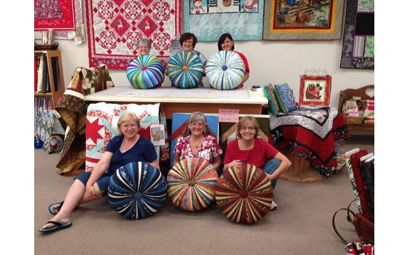 Photo of group of people holding up their Tuffet Footstools