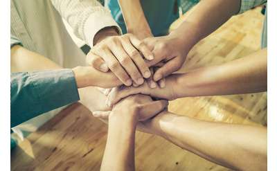 Photo of many hands forming teamwork pose