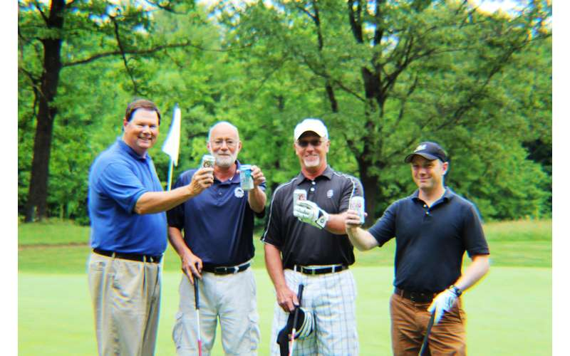 foursome of golfers with beer