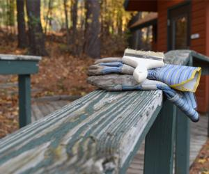 paintbrush and work gloves on a railing