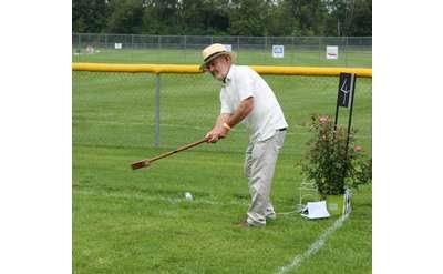 man hitting croquet ball