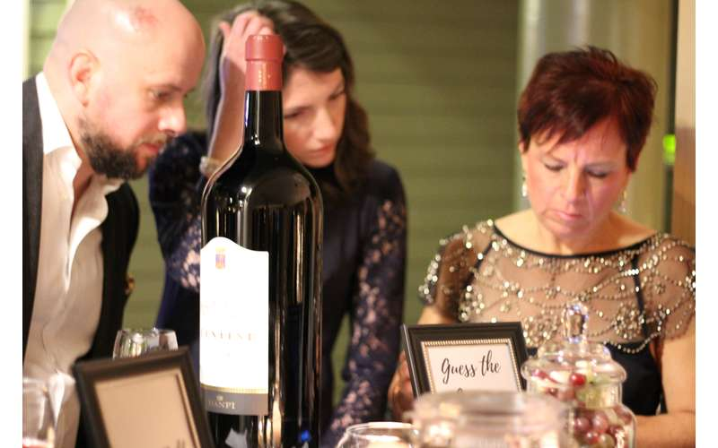 group of people looking at paper next to large bottle of wine