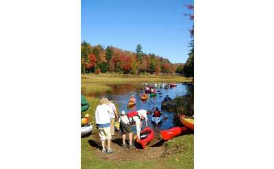 people by paddles by water in the fall