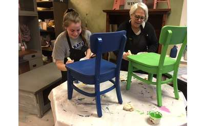 women painting chairs