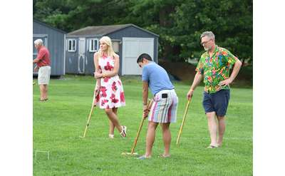 man taking shot at croquet while couple looks on