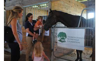 thoroughbred foundation sign and people and horse