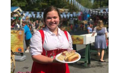 woman in german attire holding brats
