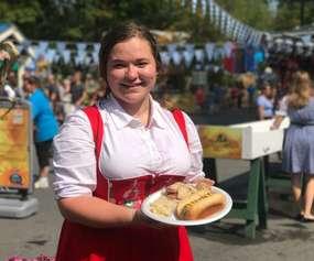 woman in german attire holding brats